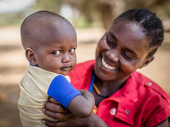 Operatore Save the Children con bambino beneficiario